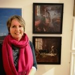 Gill Drew stands in front of her two paintings